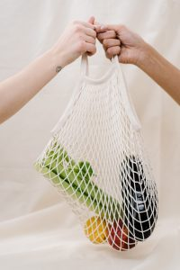 Two hands holding a bag with celery eggplant apple and lemon
