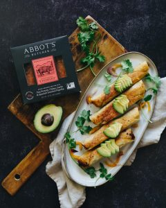 plate of abbots vegan chorizo taquitos garnished with cilantro and avocado