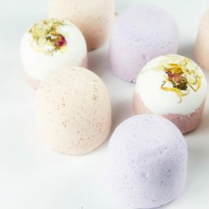 different coloured Newport's Naturals bath bombs two topped with dried flowers